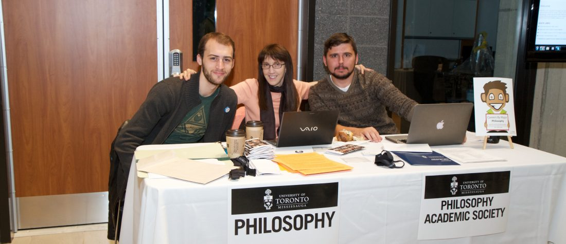Two students with Diana Raffman at a presentation table