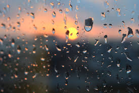 Raindrops on a window with sunset in back