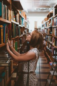 A female student browses a bookshelf.