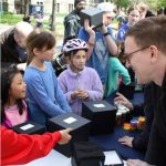 L: the philsophy team poses at their science rendezvous booth; R: Michael Miller chats with kids.