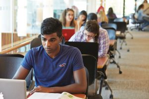 Students study at desks in a library.