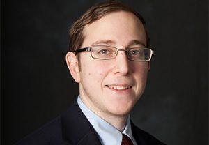 Head shot of Aaron Segal in a suit