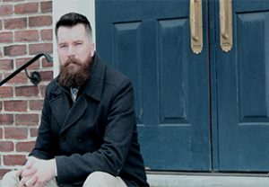 Daniel Scott Walsh sitting on steps in front of a blue door