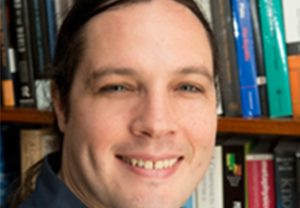 Close-up of David Wallace in front of bookshelf