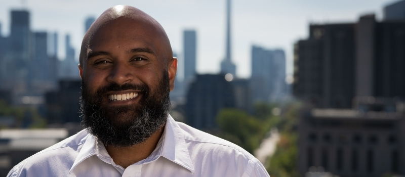 Head shot of a smiling Eric Correia in front of the Toronto skyline