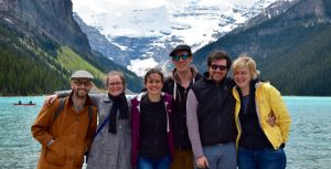 Six graduate students pose in fron of the rocky mountains.