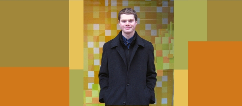 Hamish Russell in front of a colorful mosaic wall