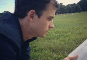 John Morrison reads a book while sitting on grass.