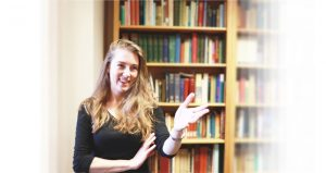 Lu-Vada Dunford gesturing toward the viewer standing in front of a bookcase