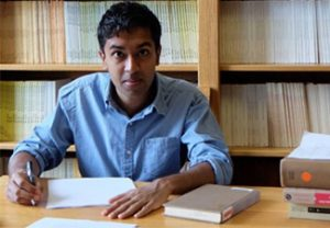 Manish Oza at a desk with bookshelves in the background
