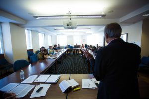 Mohan Matthan stands in front of a group of PhD program students, lecturing.