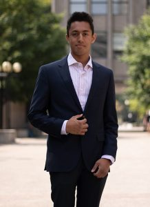 Ritvik Singh, three-quarter portrait in a suit on a university campus