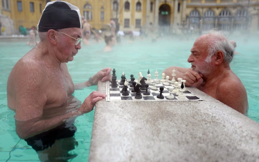 Two white-haired men play chess in public baths in Budapest.
