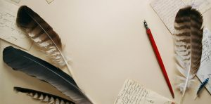 Two feather pens sit next to a piece of handwritten paper.