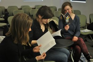 Three students read issues of Noesis journal