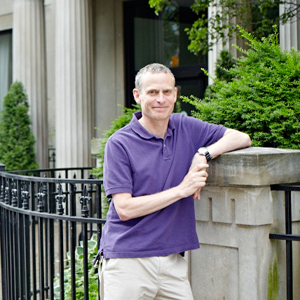 Arthur Ripstein in a purple polo shirt casually leaning on the wall in front of the Jackman Humanities Building