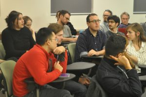 Grad students and faculty in discussion at a colloquium