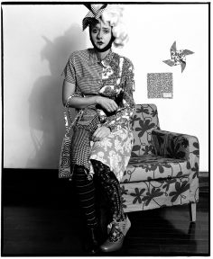 woman in costume seated on armchair