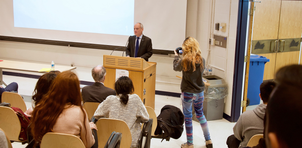 U of T President Meric Gertler addresses a lecture hall of conference attendees